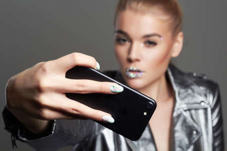 fashion beautiful woman with crystals on lips wearing silver jacket doing selfie. beauty make-up blonde girl make a picture