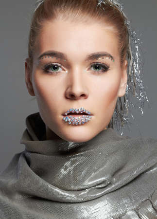 fashion portrait of beautiful woman with crystals on lips. beauty make-up blonde girl looking in camera 免版税图像