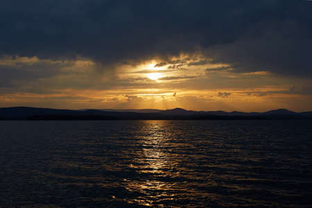 beautiful sunset on the lake. the sun is shining from behind the clouds and mountains 免版税图像