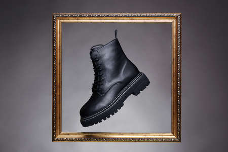 black boots in golden Frame. fashion shoes still life. art photo in the studio 免版税图像