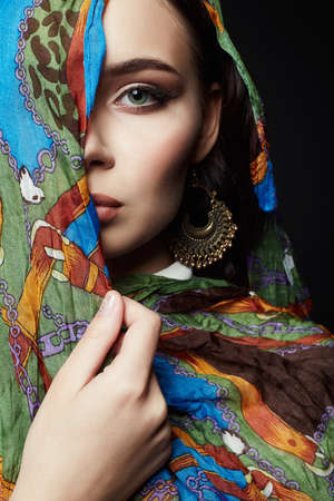 closeup portrait of beautiful young woman in color veil and jewelry. fashion oriental style girl in colorful hijab 免版税图像