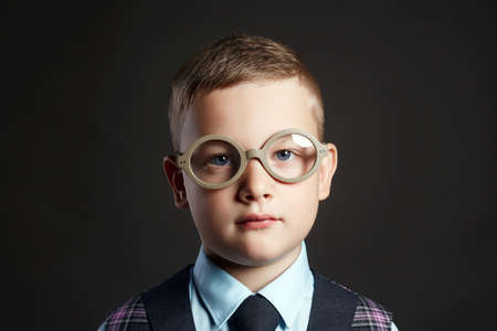 close-up portrait of smart little boy in glasses. child in suit 免版税图像