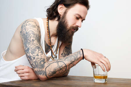 man with beard and tattoo drinking whiskey. bearded hipster boy in Bar 免版税图像