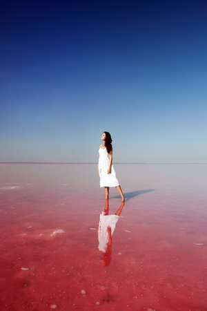girl in white dress standing in the water on pink salt lake.