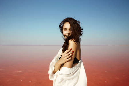 beautiful girl on pink salt lake. vacation young brunette woman in sunny day