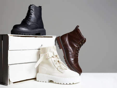 different Trendy boots with white wooden box. fashion shoes still life