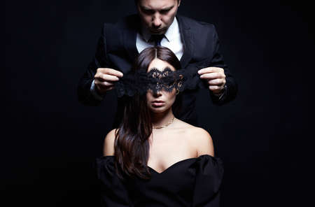 beautiful woman in dress and mask in the hands of man in a suit. Couple over black background. Adorable, elegant girl seducing her handsome boyfriend