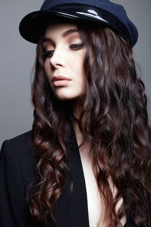 Fashionable beautiful Girl in Hat. Stylish pretty young woman with Healthy Curly Hair Foto de archivo