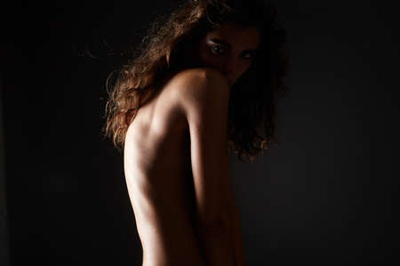 Female Back Silhouete. Naked girl with curly Hair. Nude Beautiful young woman with curls hairstyle 免版税图像