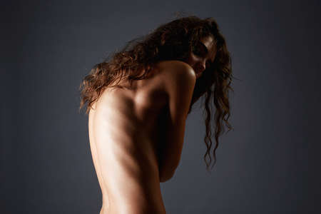 Female Back. Naked girl with curly Hair. Nude Beautiful young woman with curls hairstyle