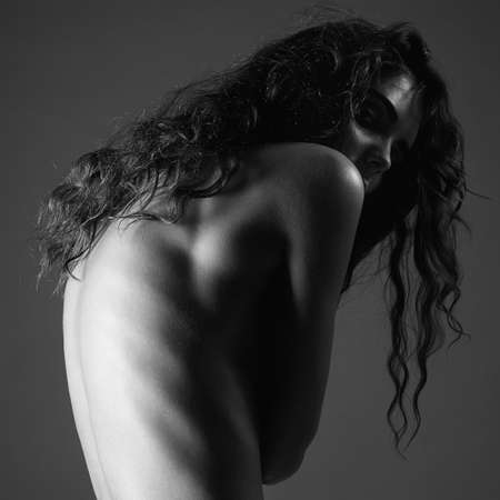 Nude Female Back. Naked girl with curly Hair. Black and white art portrait 免版税图像