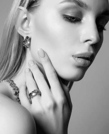 jewelry on beautiful girl. young blonde woman with make-up and jewels accessories. Black and white Beauty Fashion Portrait