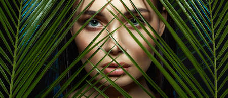 beautiful girl in palms. Beautiful woman with Make-up. Beauty Portrait. wild woman in Jungle