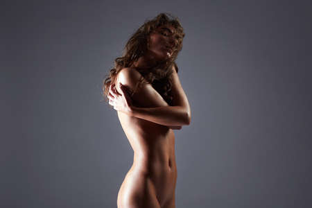 Female body Silhouete. Naked girl with long curly Hair. Nude Beautiful young woman with curls hairstyle
