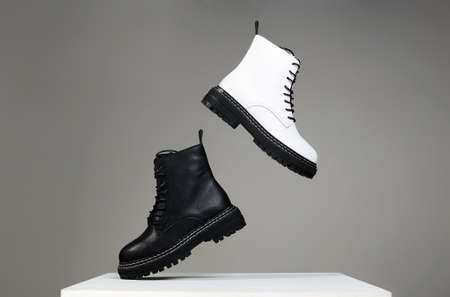 Black and white boots in the air. fashion shoes still life. stylish photo in the studio
