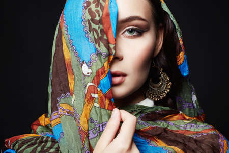 closeup portrait of beautiful young woman in color veil. fashion oriental style girl in colorful hijab