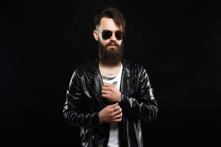 fashionable tattooed handsome man in sunglasses. Brutal bearded Sexy boy in leather coat 免版税图像
