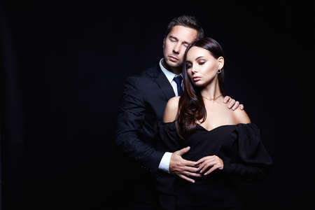 beautiful woman in evening dress in the hands of man in a suit. Lovely Couple over black background. Adorable, elegant girl seducing her handsome boyfriend