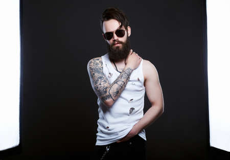 handsome man in sunglasses. Brutal bearded hipster boy in glasses and vintage torn dirty shirt. beard, haircut, tattoo 免版税图像 - 159505825