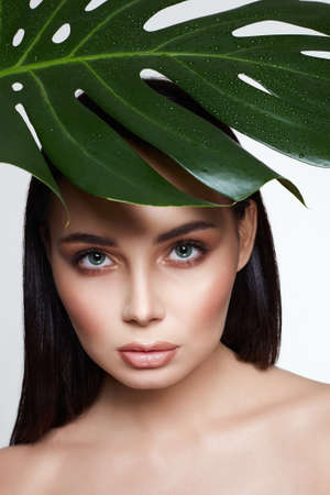 beautiful girl in palm leaves. Beautiful young woman with Make-up. Beauty Portrait. Natural cosmetics