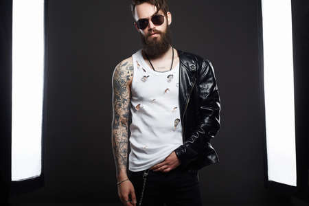 Tattooed handsome Bearded Man in sunglasses and Leather. Brutal hipster boy with tattoo. Male model in Photostudio
