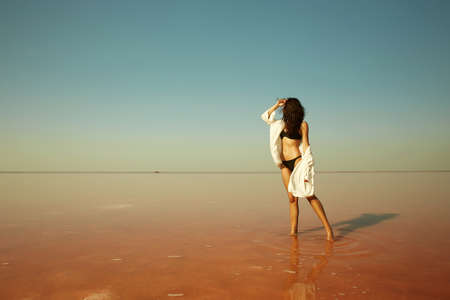 beautiful girl standing in the water on a pink salt lake. relaxing young woman in bikini 免版税图像