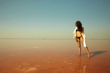 beautiful girl standing in the water on a pink salt lake. relaxing young woman in bikini 免版税图像 - 159517025