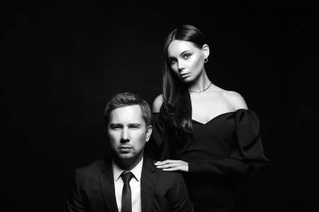 beautiful woman in evening dress with man in a suit. Couple over black background. Adorable, elegant girl with her handsome boyfriend