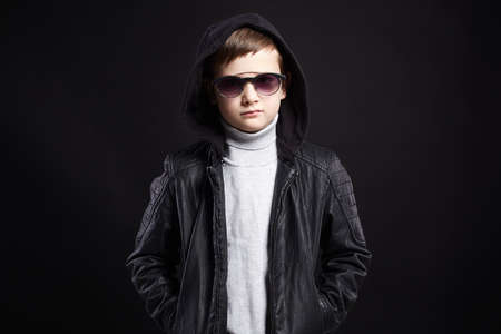 funny little boy in hoodie and sunglasses. stylish kid in leather coat