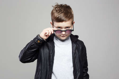 funny little boy in hoodie and sunglasses. happy kid in leather coat 免版税图像 - 164856057