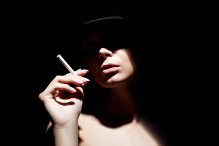 Beautiful woman in a hat and with a cigarette. Retro style portrait. Lady girl with face under shadow