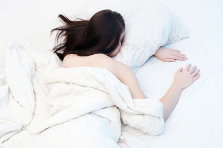Lifestyle portrait of cute girl sleeping on bed. beautiful sensual woman in white morning bed