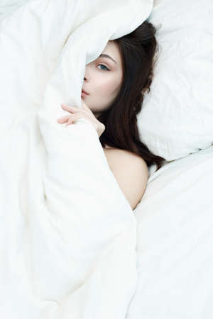 Lifestyle portrait of brunette girl on bed. beautiful sensual woman in white morning home