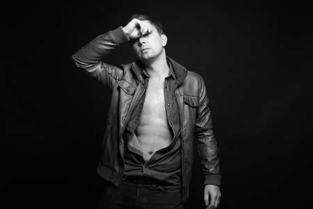 Fashion young Man in leather coat. stylish sexy Handsome Boy black and white portrait