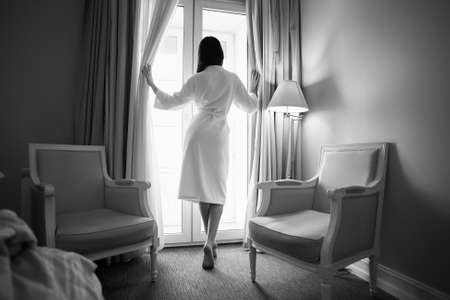 Woman in bathrobe stay near the window in hotel room. Female back. Black and white photo