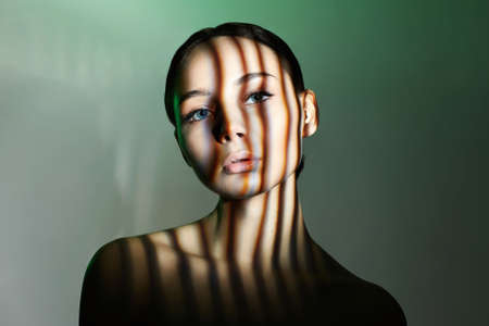 light on the face of beautiful girl. sensual young woman in shadows