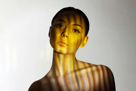 color light on the face of beautiful girl. sensual young woman in shadows