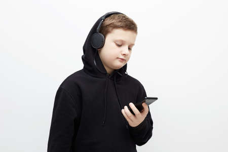 little boy in hood and headphones. stylish teenager boy listening music by phone. Child