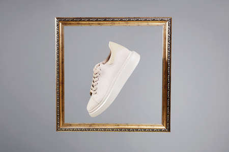beige sneakers in golden Frame. fashion shoes still life. stylish photo in the studio
