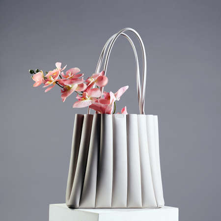 Stylish Leather Handbag with Flowers, fashion still life. Female Bag