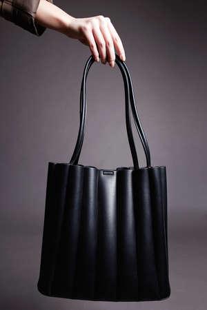 woman's hand holding Black Handbag. fashion Bag still life. stylish photo in the studio 免版税图像