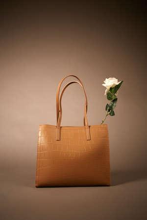 Stylish Leather Handbag with Flower, fashion still life. Rose in Female Bag