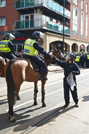 fascism: Sheffield, UK - June 8, 2013 - Mounted policeman receives water at English Defence League and United Against Fascism protest