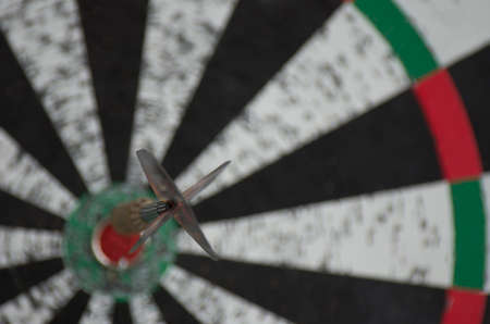 An old dartboard with a dart hit the bullseye Stock Photo