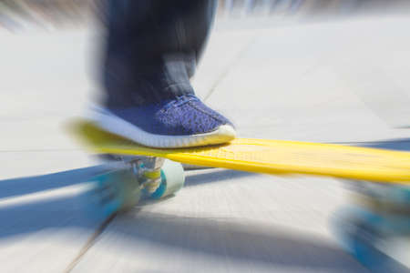 rowdy: A teenager rides on a yellow pennyboard. Radial zoom blur action effect.