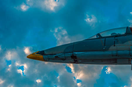 Part of a jet fighter monument against dramatic sky at sunset