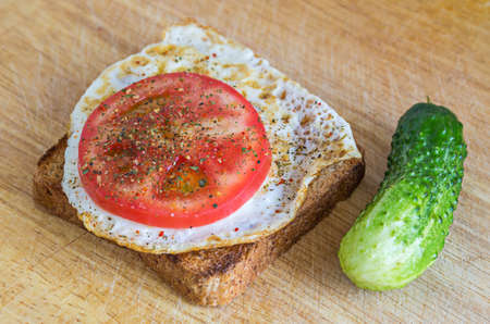 whole wheat toast: Healthy breakfast: fried egg on a whole wheat toast with a slice of tomato, seasoning and fresh green cucumber on a wooden chopping board Stock Photo