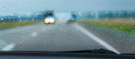 Wazig verkeerslichten gezien door de regen druppels op de voorruit van een auto op een snelweg