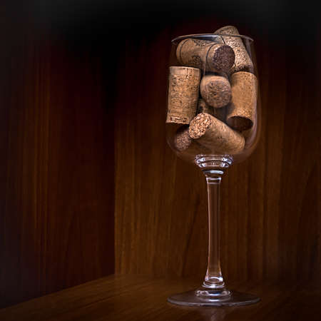 Catering, party concept: close-up image of wine glass with corks on a dark wooden background. Selective focus. Stock Photo