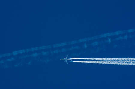Transportation competition concept: a jet airplane crossing other plane's white contrail against blue sky background with copy space